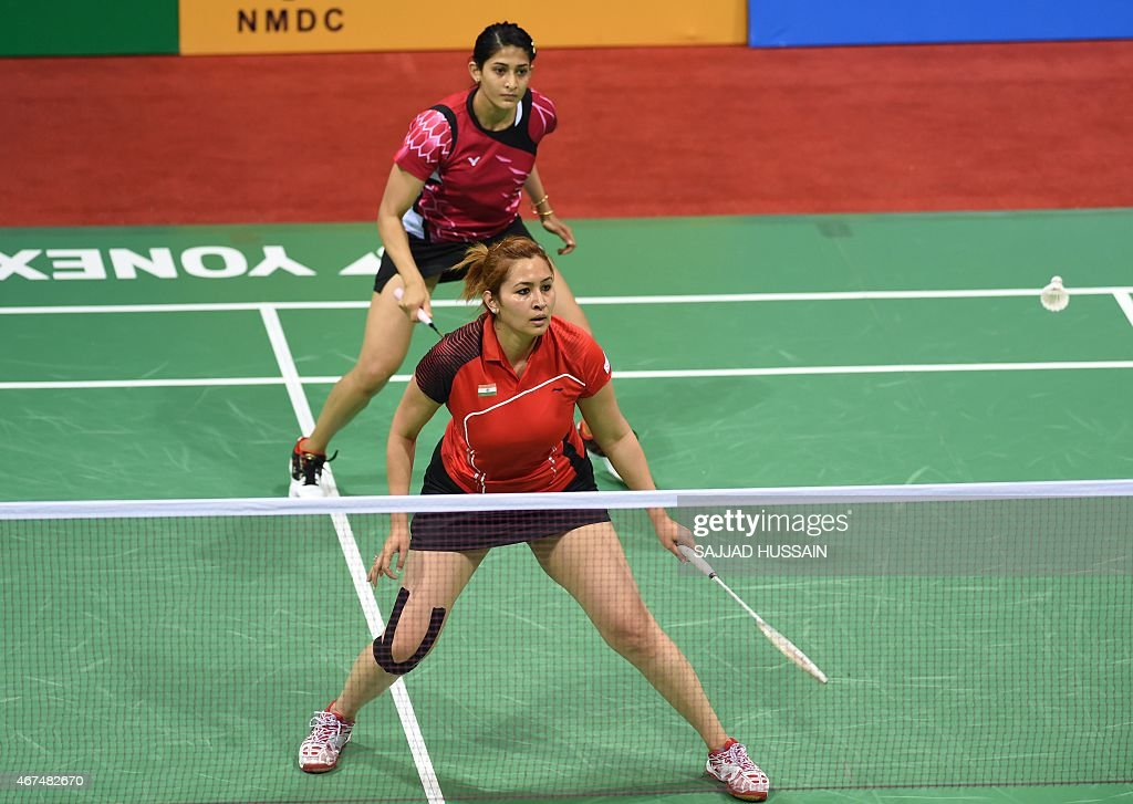 Ashwini Ponnappa of India looks on as <a gi-track='captionPersonalityLinkClicked' href=/galleries/search?phrase=Jwala+Gutta&family=editorial&specificpeople=795812 ng-click='$event.stopPropagation()'>Jwala Gutta</a> (front) returns a shot to Ou Dongi and Xiaohan of China during their women's badminton doubles match at the Yonex-Sunrise India Open 2015 at the Siri Fort Sports Complex in New Delhi on March 25, 2015. AFP PHOTO / SAJJAD HUSSAIN