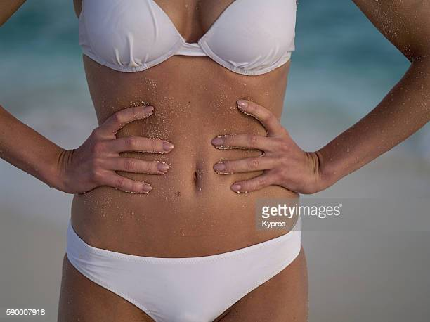 Asia, Maldives, Close Up Of Young Caucasian Woman's Tummy On A Tropical Beach Alone