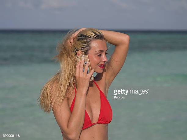 Asia, Maldives, Young Caucasian Woman Making Phone Call With Smartphone On Tropical Beach 'n