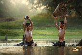 Asia Two boys joyful catch fish in the lake this is the lifestyle of children in Countryside Thailand.