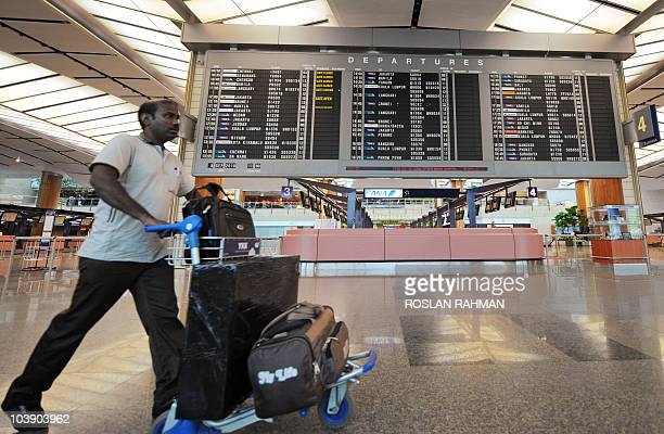 AsiaaviationtraveltourismeconomyFOCUS by Martin Abbugao A traveller pushes his luggage along the departure hall at Changi International Airport in...