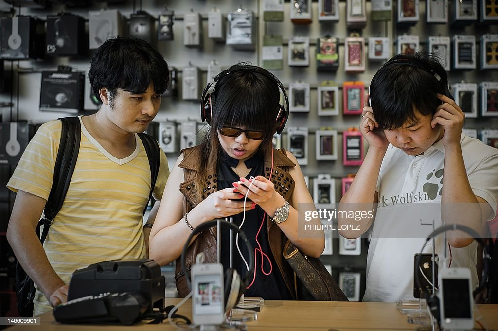 Asia-music-HongKong-technology-entertainment, FEATURE by David Watkins In a picture taken on June 18, 2012, a woman listens to a music track as she tries a mp3 player in a shop in Hong Kong. Technology is the new rock'n'roll as smartphones and digital services transform the music industry. But Asia, home to some of the world's largest consumer markets, presents big hurdles to an industry looking to beat piracy. AFP PHOTO / Philippe Lopez