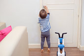 Asian 18 months / 1 year old toddler baby boy standing on tiptoes at home, Kid reaching up try to open / close door knob, Child want to escape to play, explore outdoor, Security and Safety Concept