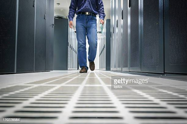 Asian administrator is walking in the data  center room.