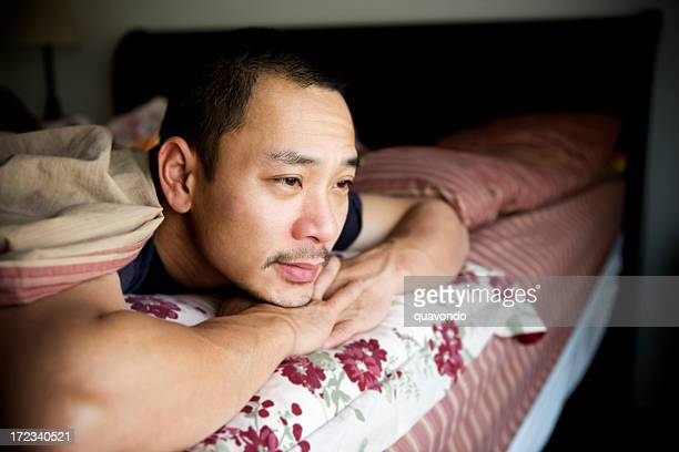 Asian Adult Man Depressed in Bed at Home, Copy Space