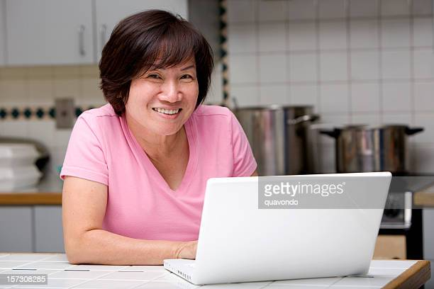Asian Adult Woman Using Laptop in Home Kitchen, Copy Space