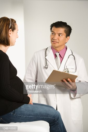 Asian American male doctor examining Caucasian pregnant female patient. : Stock Photo
