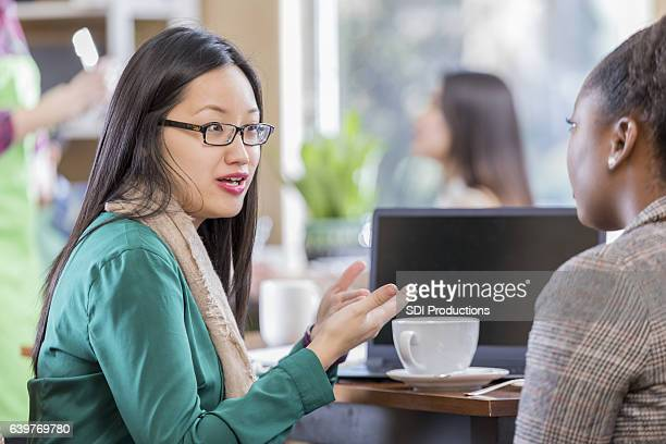 Asian and African American female colleagues meet for coffee