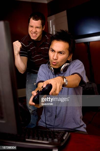 Asian and Caucasian Male Desktop Gamers at Home