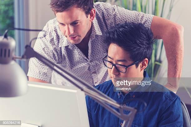 Asiatische und kaukasischen Männer arbeiten zusammen Blick auf computer.