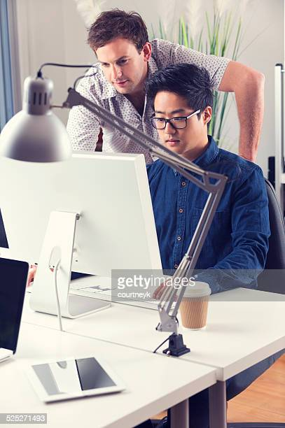 Asian and Caucasian men working together looking at computer