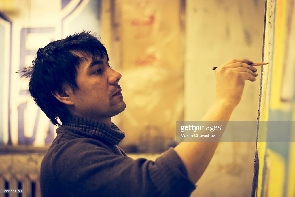 Asian artist drawing on canvas in studio