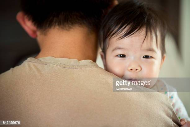 Asian baby boy carried by father.