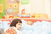 Asian baby girl playing in a ball pool