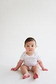 Asian baby girl sitting on floor
