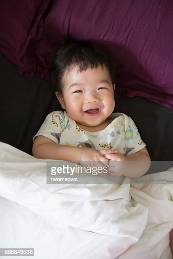 Asian baby laughing in bed.