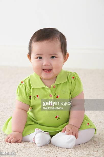 Asian baby sitting smiling sitting on the floor