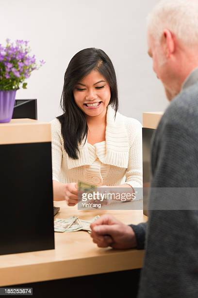 Asian Bank Teller Handing Cash, Providing Customer Service at Counter