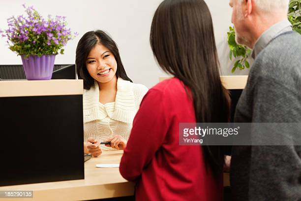 Asian Bank Teller Servicing Banking Customer Transaction Over Retail Counter