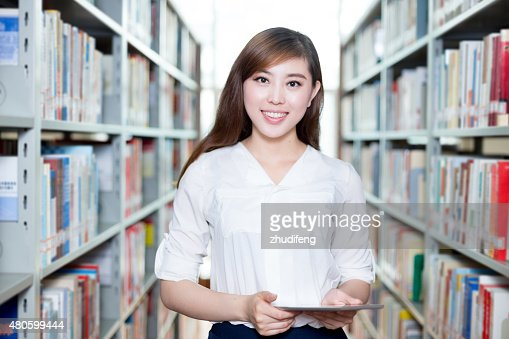 Asian beautiful female student using tablet in library : Stock Photo