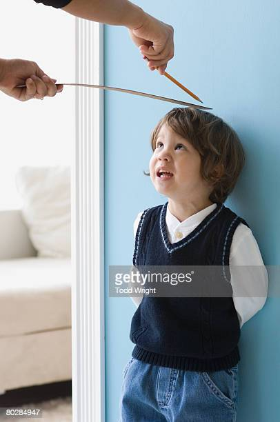 Asian boy having height measured on wall