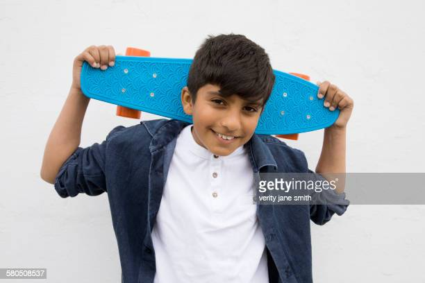 Asian boy holding skateboard