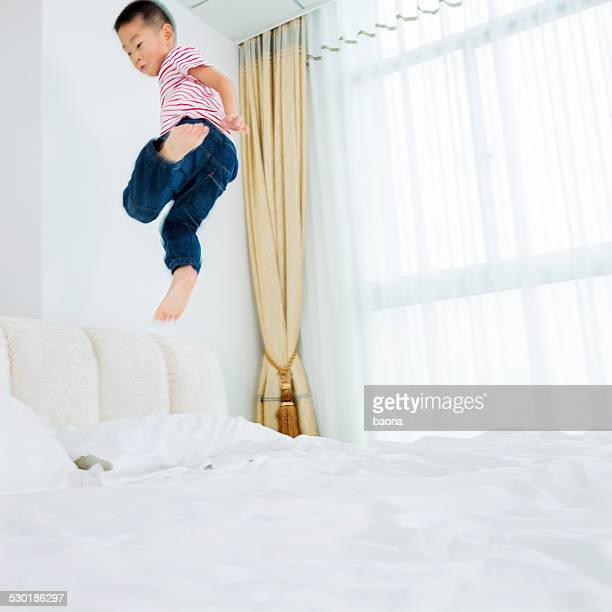 asian boy jumping on the bed