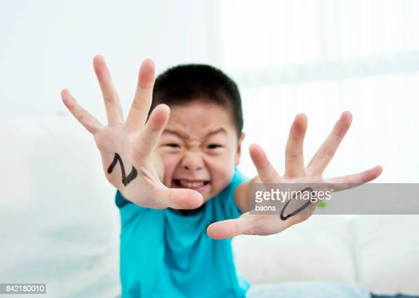 Asian boy makes a stop gesture