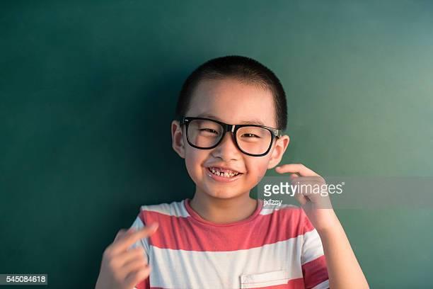 Rapaz asiático junto de chalkboard em frente