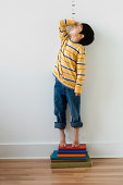 Asian boy standing on books in front of height markers