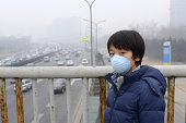 Asian child protects himself against air pollution by wearing mouth mask