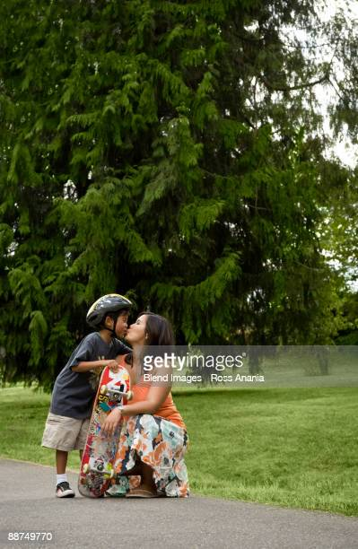 Asian boy with skateboard kissing mother
