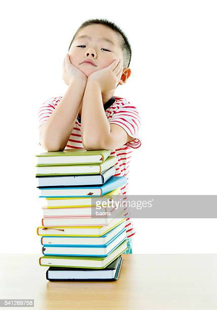 Asian boy with stack of books