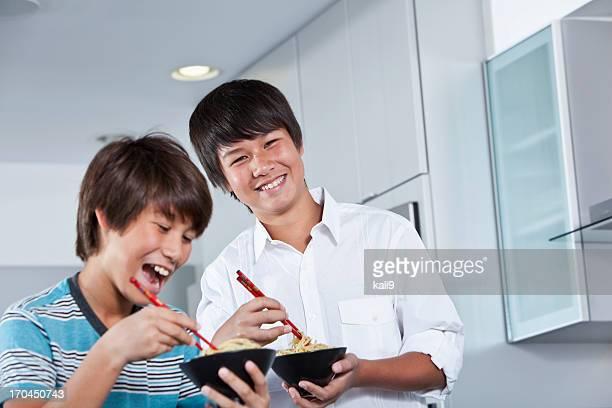 Asian boys eating noodles