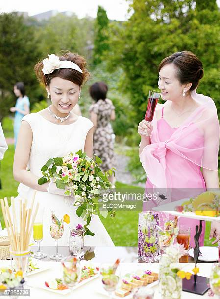 Asian bride and friend talking at party