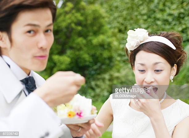 Asian bride and groom eating cake