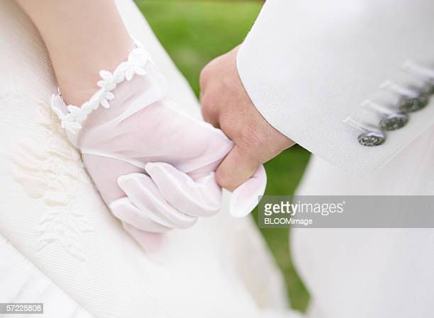 Asian bride and groom hand holding