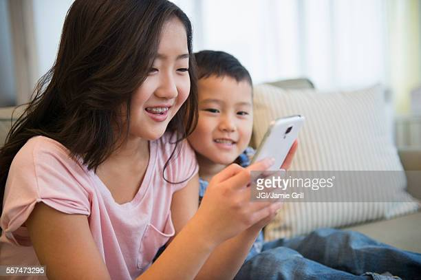 Asian brother and sister using cell phone on sofa