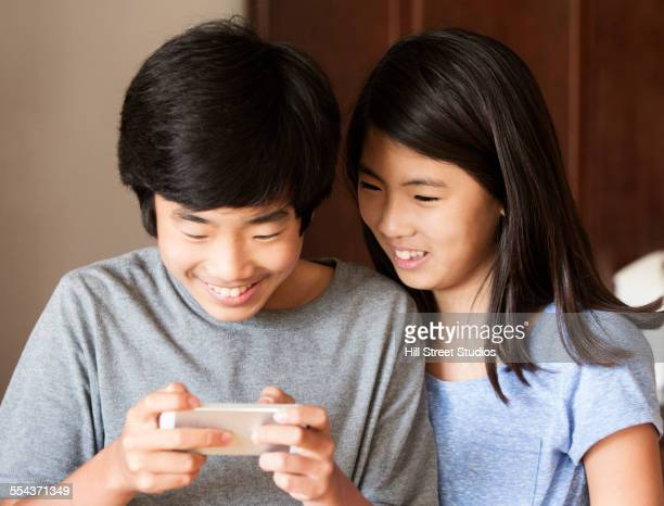 Asian brother and sister using cell phone