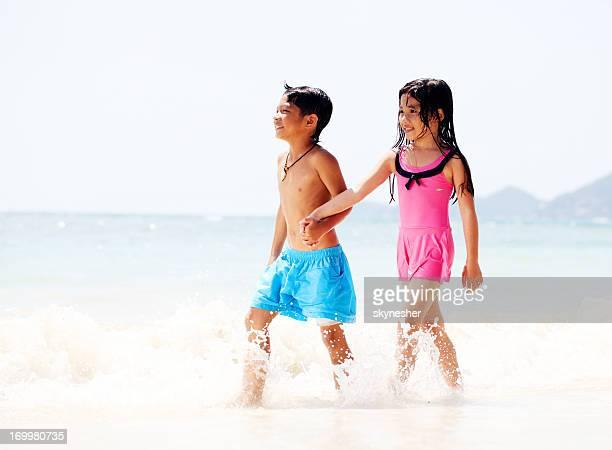 Asiatische Bruder und Schwester zu Fuß im Wasser