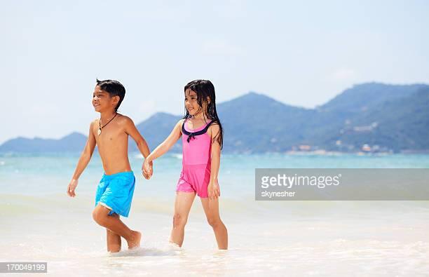 Asiatische Bruder und Schwester zu Fuß im Wasser.