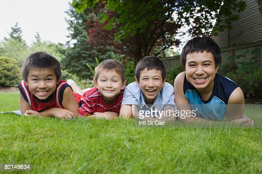 Asian brothers laying in grass