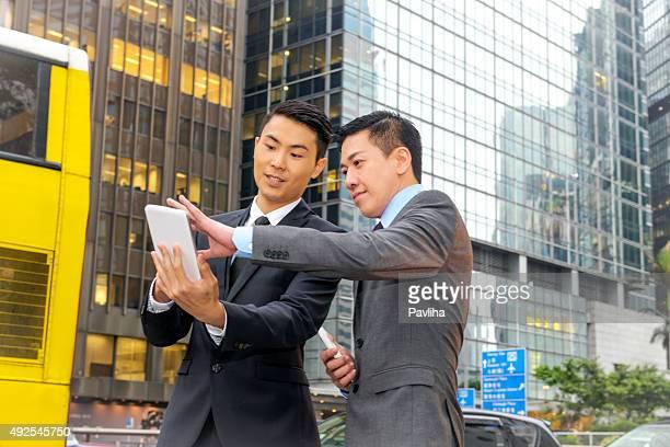 Asiatischen Geschäftspartnern mit Mobile Geräte, Hong Kong Street, China