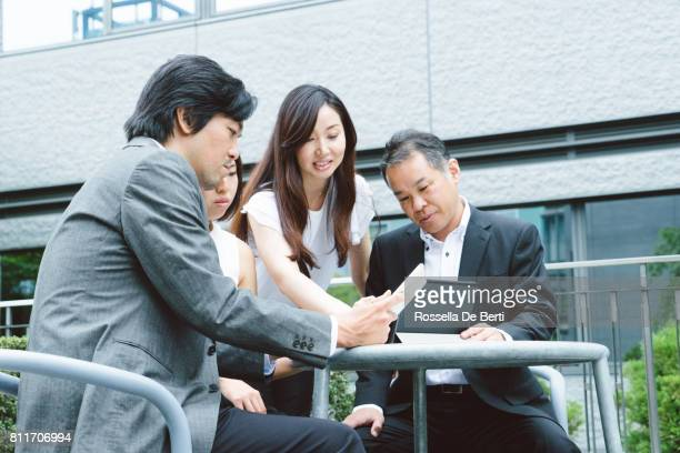 Asian business people having a meeting outdoors