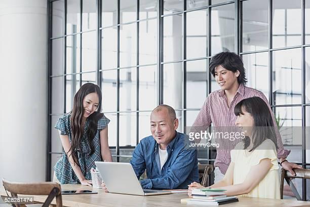 アジア実業家仕事のミーティングを見ているノートパソコン