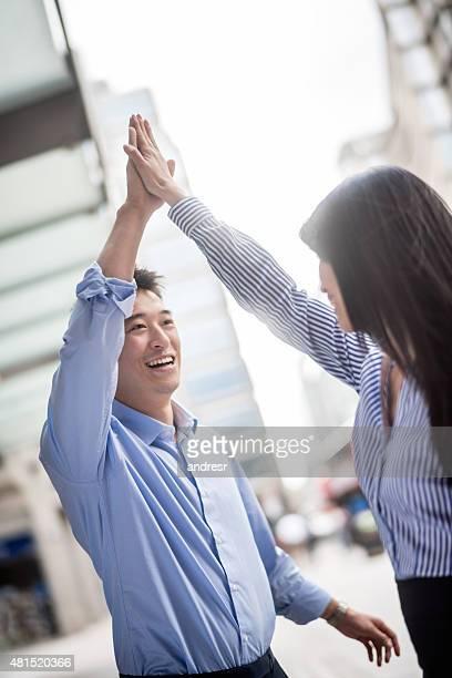Asian business team giving a high-five