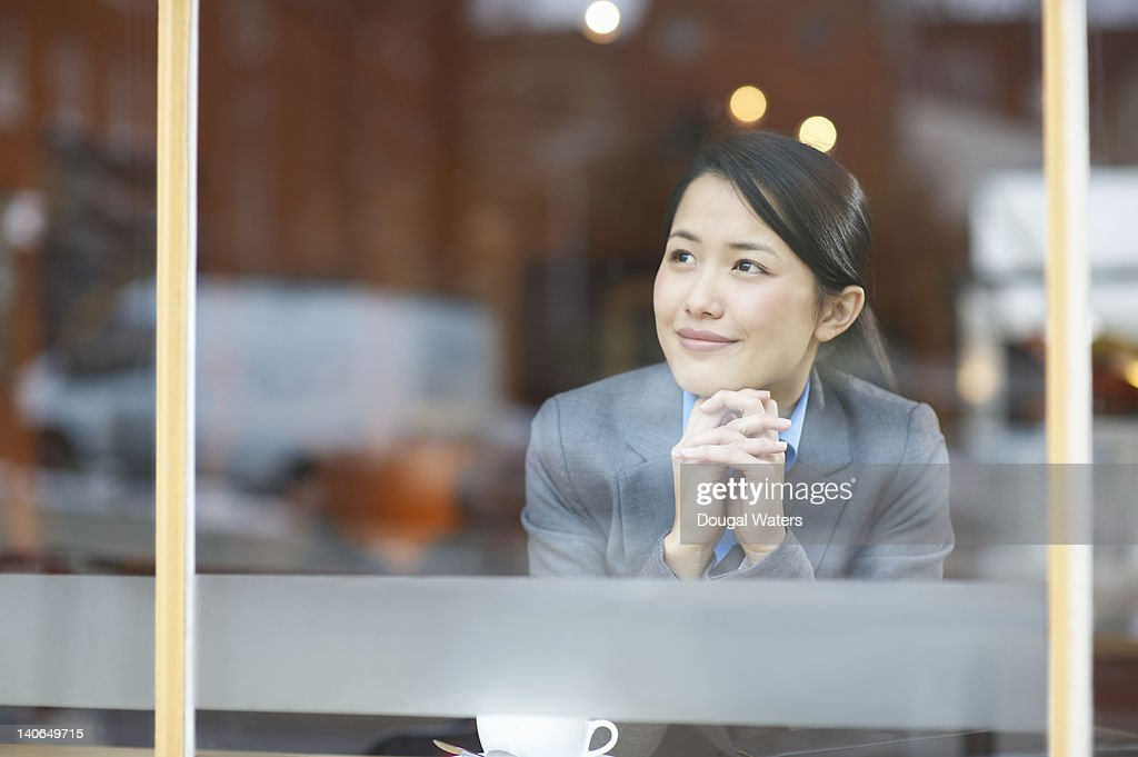 Asian business woman looking out of cafe window. : Stock Photo
