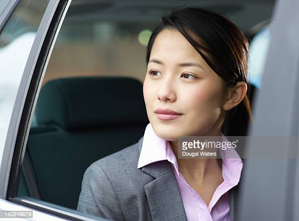 Asian business woman looking out of car window.