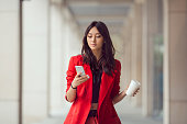 Young Asian woman with smartphone standing against street blurred building background. Fashion business photo of beautiful girl in red casual suite with phone and cup of coffee