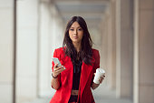 Young Asian woman with smartphone standing against street blurred building background and looking. Fashion business photo of beautiful girl in red casual suite with phone and cup of coffee